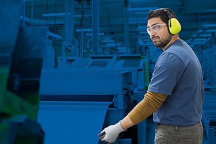 Safety professional man wearing hearing and eye protection while conducting a risk assessment