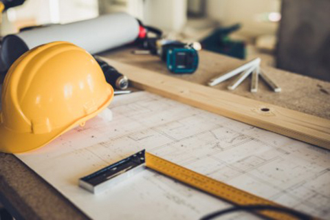 Yellow hardhat resting on table with blueprints