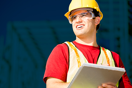 Construction safety professional man in a red shirt and PPE holding a clipboard