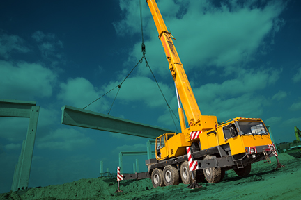 A mobile crane on a construction job site with a blue background