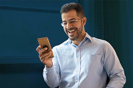 Smiling safety professional man in a blue shirt and glasses using his smart phone for a video call with senior leaders