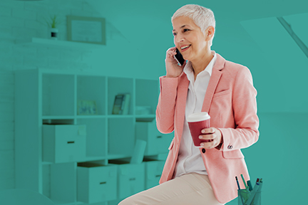 Safety professional woman with short white hair and a pink blazer is sitting on her desk and talking on the phone