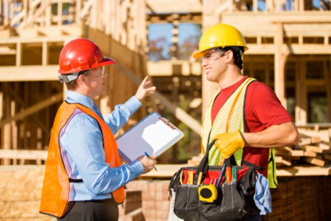 Two men in hardhats standing in a worksite discussing safety