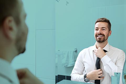 Man looking in mirror adjusting his tie