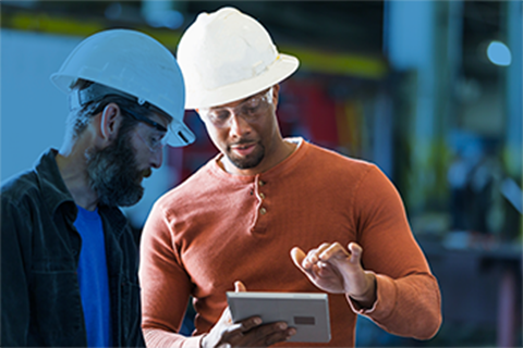 One older and one younger man on a construction site with hard hats looking at safety information on a tablet computer